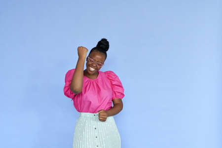 Excited young african woman celebrating win in yes isolated on lilac background.