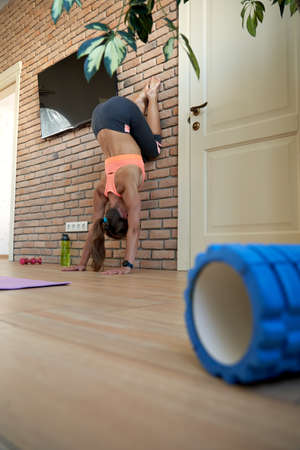 Fit yogi woman wear sportswear doing handstand exercise at home at the wall.