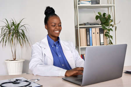 Smiling african american female doctor gp using laptop computer at workplace. Standard-Bild