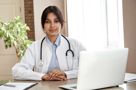 Confident indian female doctor wear white coat looking at camera at workplace.