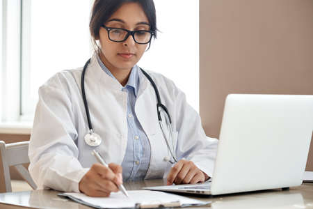 Indian female doctor filling medical form working with laptop at workplace.