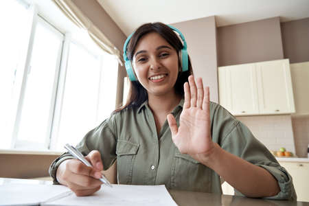 Happy indian online teacher looking at webcam video call remote teaching.
