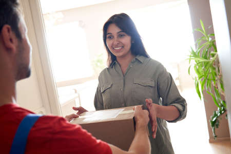 Happy indian woman customer receiving courier delivery box standing at home. Standard-Bild