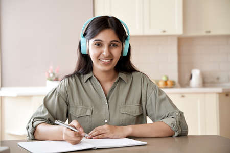Happy indian girl wear headphones look at camera study at home listen course.