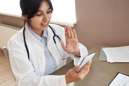 Indian female doctor video calling patient in online mobile phone app. Standard-Bild