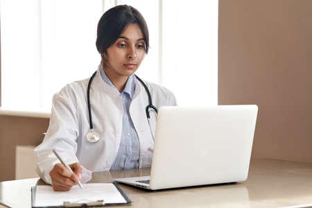 Indian female doctor watching online training webinar on laptop at work.