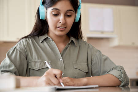 Indian girl wearing headphones writing homework listening audio course at home.
