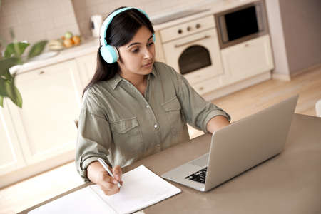 Indian woman student wear headphones watching online class seminar at home.