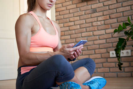 Fit sporty woman holding phone using fitness yoga application at home.
