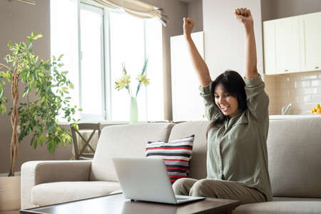 Excited indian woman celebrating online win looking at laptop at home.