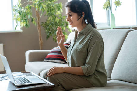 Happy indian woman online tutor wearing headset making conference video call. Standard-Bild