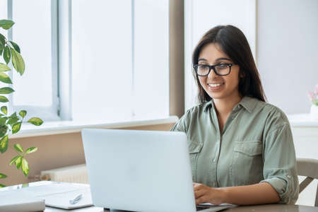 Happy indian young woman using laptop computer work study at home office.