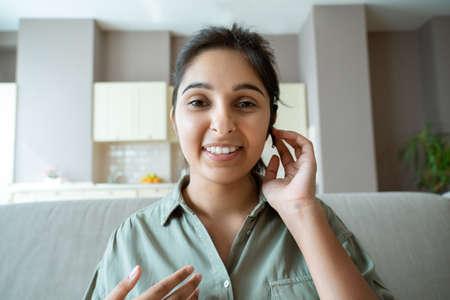 Indian lady customer support operator wear headset look at webcam. Headshot Standard-Bild
