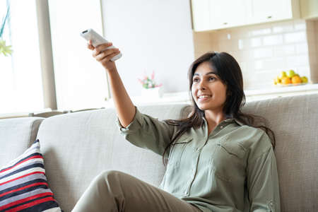 Happy indian woman turns on air conditioner system relaxing on couch at home.