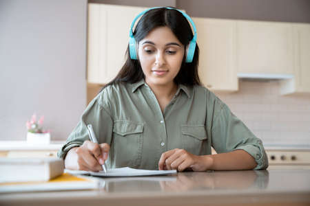 Indian girl wear headphones writing in notebook listening audio lesson at home.