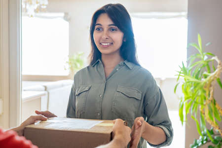 Smiling indian woman customer buyer receiving courier delivery box at home.
