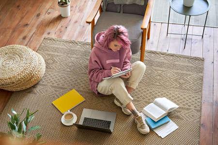 Teen girl studying online on laptop writing notes sit on floor, top view. Standard-Bild