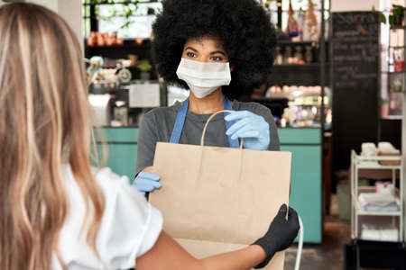 African female cafe worker wear face mask giving takeaway food bag to customer. Stock Photo