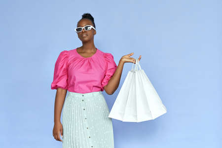 Fashion black woman wear sunglasses holding shopping bags isolated on violet. Stock fotó