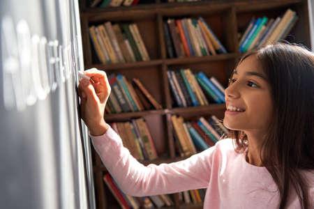 Happy indian latin kid school girl pupil holding chalk writing on blackboard.