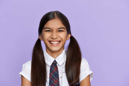Funny positive indian kid primary school girl laughing isolated on background.