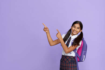 Happy indian school girl pointing advertising isolated on violet background.