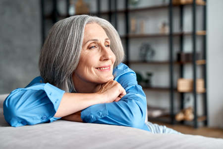 Happy relaxed mature old woman resting dreaming sitting on couch at home.