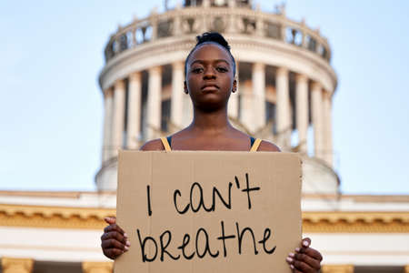 Young african woman activist stand outdoor hold empty blank sign protesting on street. Black female protest against discrimination racism for empowerment, civil rights, racial equality justice concept