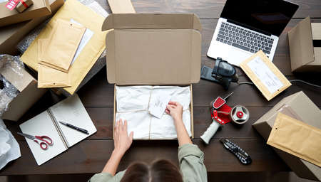 Top view of female online store business owner packing ecommerce shipping box.