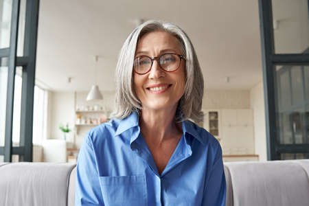 Smiling mature older woman looking at camera, webcam headshot.