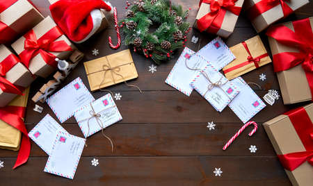 Merry Christmas decorated wooden table with envelopes and gifts boxes, Top view. Stock Photo