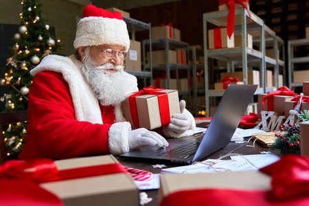 Santa Claus holding gift using laptop computer sitting at workshop table.