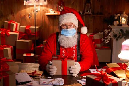 Santa wearing face mask holding Christmas gifts on xmas eve.