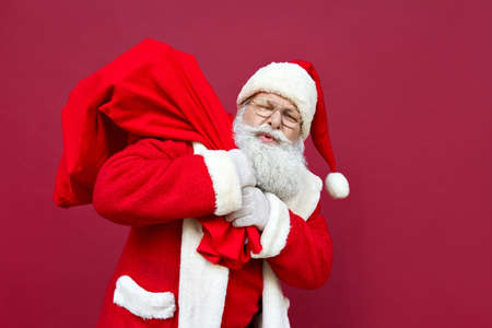 Tired Santa Claus feeling back pain holding heavy bag on red background.