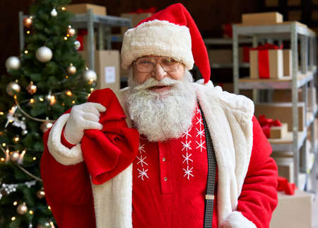 Happy Santa Claus wearing costume holding sack bag with gifts in workshop.