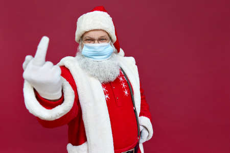 Santa Claus wearing face mask showing middle finger on red background.