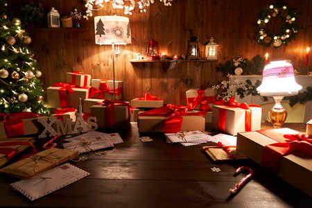 Santa workshop table with Merry Christmas tree, gift boxes pile on xmas night. Foto de archivo