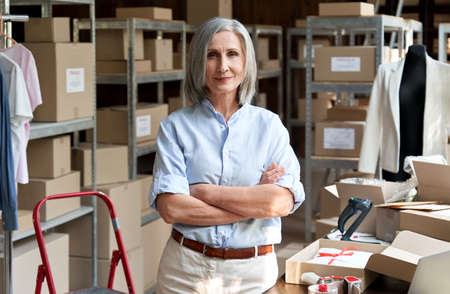 Female entrepreneur clothing store business owner in warehouse, portrait.