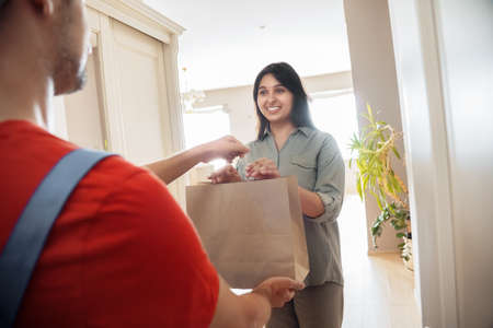 Indian woman customer takes delivery bag from courier at home.