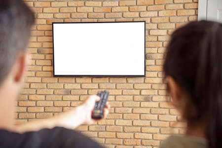 Couple holding remote control watching tv mockup white screen at home.