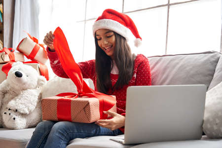 Excited indian girl wear santa hat opens gift video calling family on Christmas. Banco de Imagens