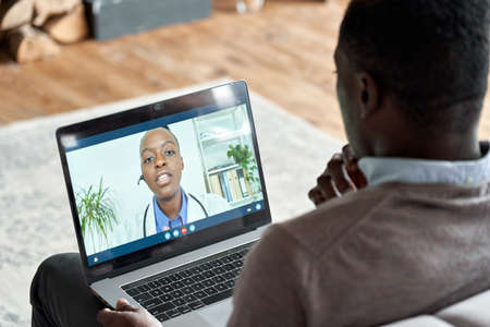 Male black patient on conference video call with female african doctor. Banco de Imagens