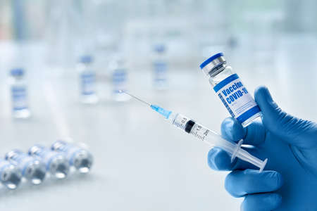Male doctor hand wears glove holding syringe and vial with covid 19 vaccine.