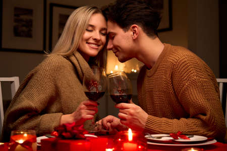 Happy couple in love clinking glasses drinking red wine having romantic dinner.