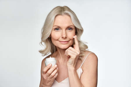 Smiling 50s middle aged woman putting facial cream on face looking at camera.