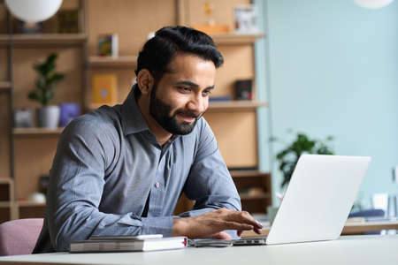 Smiling indian business man working studying on laptop computer at home office.