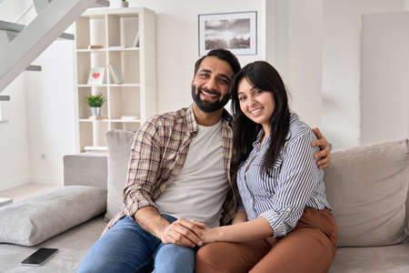 Happy indian couple hugging looking at camera sitting on couch at home. Archivio Fotografico