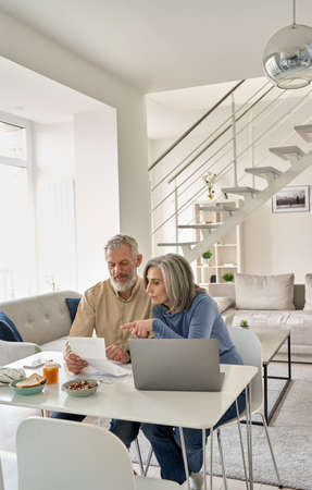 Senior mature couple checking bank documents using laptop at home.
