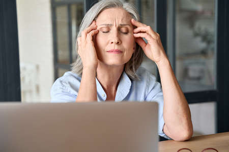 Stressed senior 60s aged massaging head at home office, suffering on workplace.