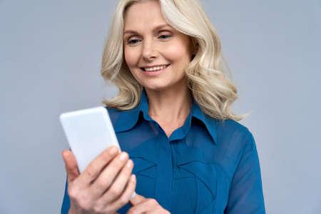 Shot of senior 50s aged blonde female manager using phone isolated on gray Imagens